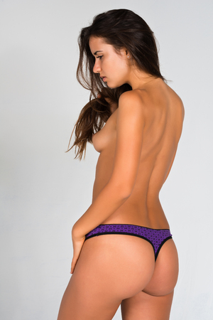 Slender young Romanian woman nude in purple and black panties photo