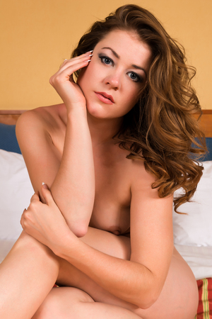 Pretty young brunette sitting nude in bed photo