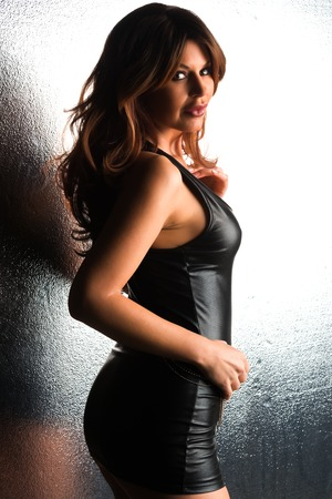 Beautiful tall brunette in a tight black leather dress