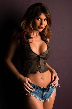 waistcoat: Beautiful tall brunette in a waistcoat and denim shorts Stock Photo