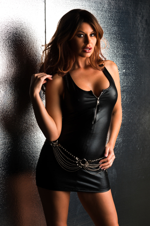 Beautiful tall brunette in a tight black leather dress photo