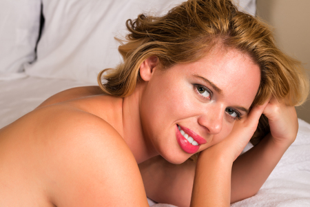 Curvy young blonde nude in bed photo