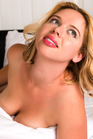 Curvy young blonde lying  in bed Stock Photo