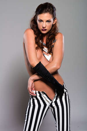 Beautiful slender topless brunette in striped pants photo