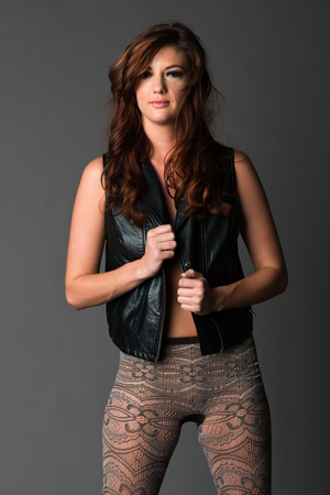 Beautiful slender brunette in a black leather vest and knit tights photo