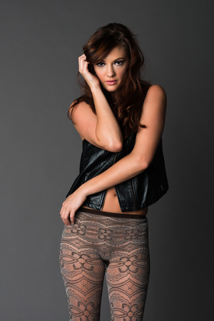 Beautiful slender brunette in a black leather vest and knit tights