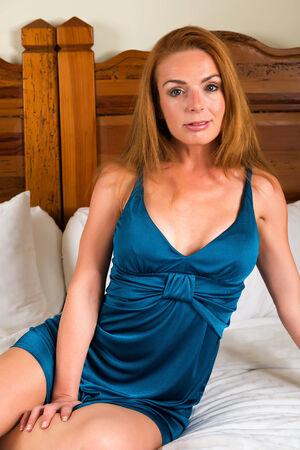 Beautiful tall redhead in a turquoise dress photo