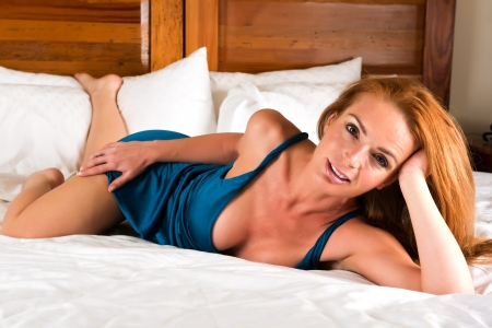 sexy bedroom: Beautiful tall redhead in a turquoise dress