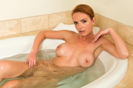femme se deshabille: Belle grande rousse dans une baignoire spa Banque d'images