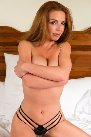 Beautiful tall redhead topless in a black thong photo