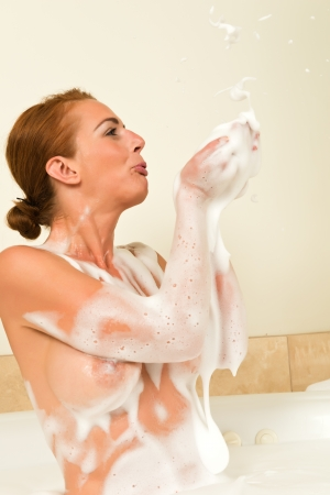 Beautiful tall redhead in a bubble bath photo