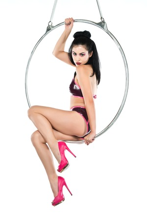 Tall slender woman suspended from an aerial hoop photo