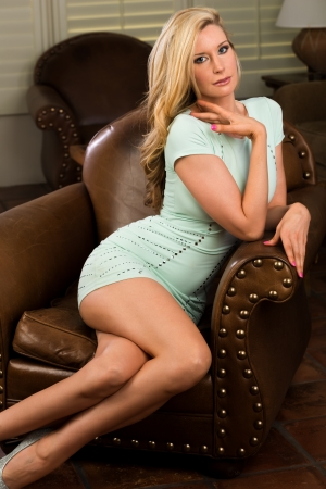Beautiful tall blonde in a tight green dress photo