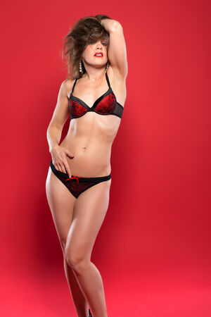 Pretty petite brunette dressed in red and black lingerie photo