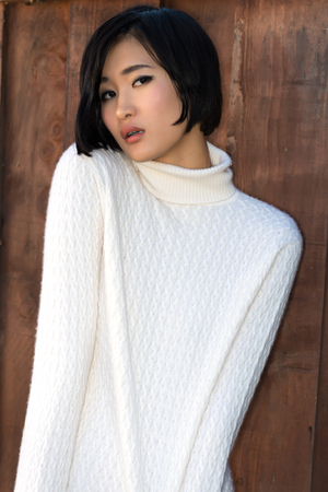 Beautiful young Japanese woman in a white knit sweater photo