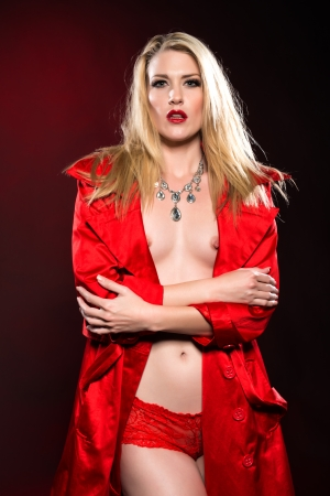 Beautiful slender blonde woman in a red raincoat