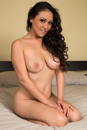ni�a desnuda: Hermosa mujer multirracial desnuda en la cama Foto de archivo