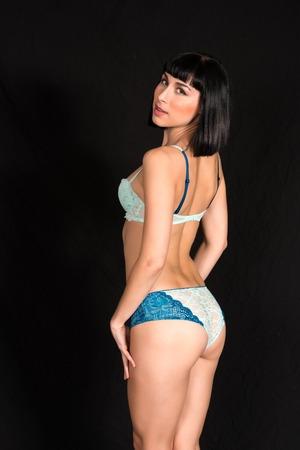 blue lingerie: Beautiful slender brunette dressed in blue lingerie
