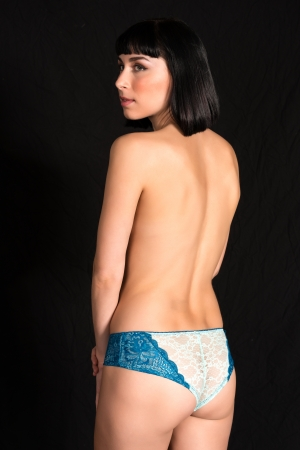 Beautiful slender topless brunette dressed in blue panties photo