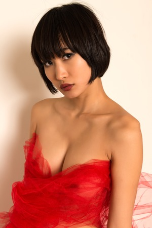 Beautiful young Japanese woman wrapped in red tulle photo