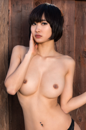 Beautiful young Japanese woman nude against a wood fence Stock Photo