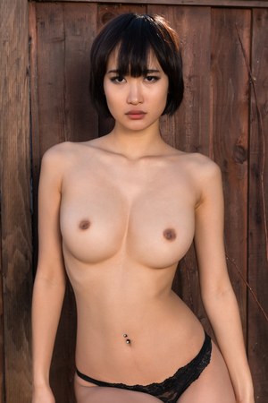 Beautiful young Japanese woman topless against a wood fence Stock Photo