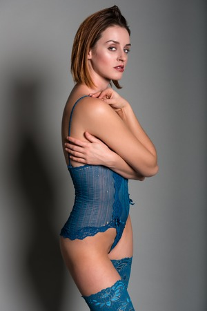 Tall young redhead in a turquoise bodysuit