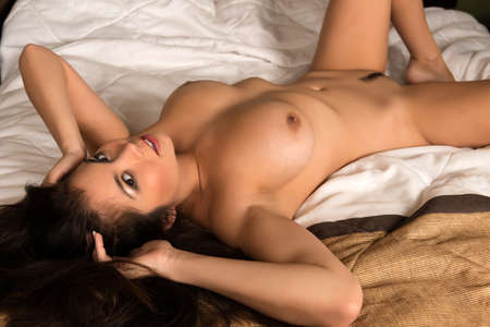 undressed young: Beautiful young Eurasian woman lying nude in bed