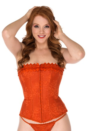 Petite freckled redhead in a orange corset