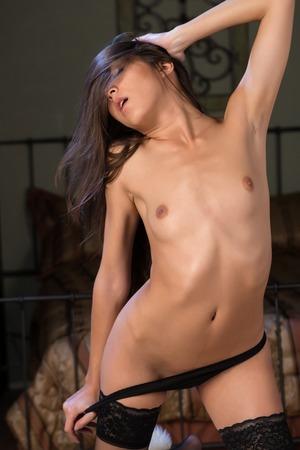Beautiful petite Eurasian woman topless in black lingerie