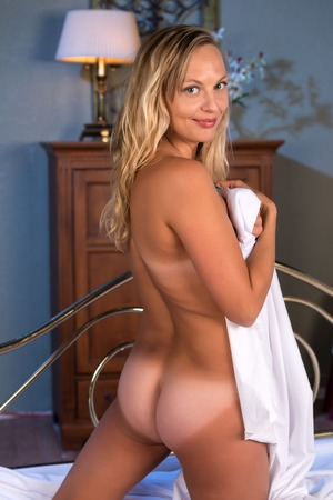 nude blonde woman: Pretty nude blonde woman covered by a bedsheet Stock Photo