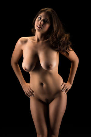 Beautiful young Eurasian woman nude in shadow