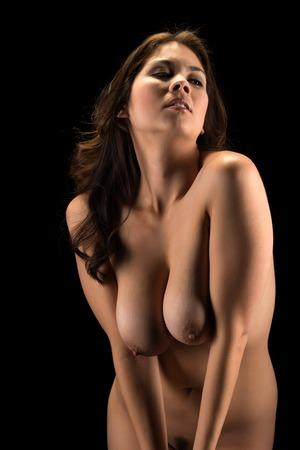 Beautiful young Eurasian woman nude in shadow