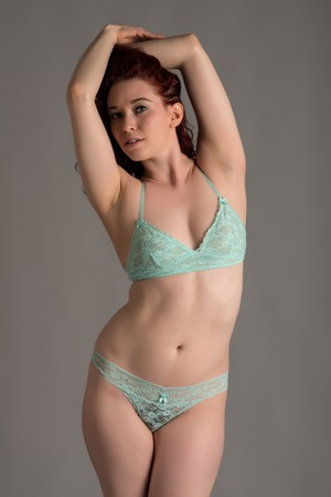 Pale redhead dressed in teal lingerie Stock Photo