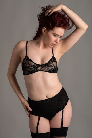 garters: Pale redhead dressed in black lingerie