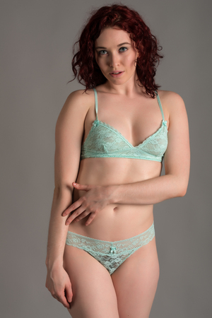 light blue lingerie: Pale redhead dressed in teal lingerie Stock Photo