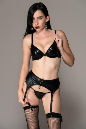 garters: Bruna piuttosto giovane, vestito di nero lingerie Archivio Fotografico