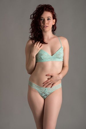 Pale redhead dressed in teal lingerie photo