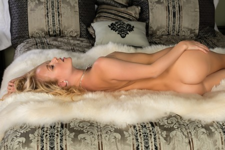 Beautiful young Hungarian blonde lying nude in bed photo