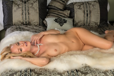 Beautiful young Hungarian blonde lying nude in bed