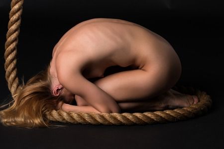 Pretty young blonde woman nude on a climbing rope Stock Photo