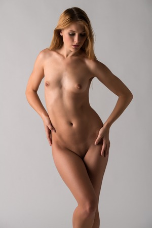 nudity: Pretty young blonde woman nude on gray Stock Photo