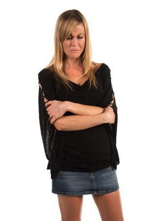 distressed: Pretty petite blonde woman in black long sleeved blouse Stock Photo
