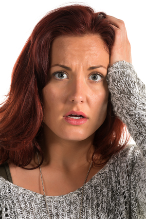 dismayed: Pretty redheaded woman in a gray sweater