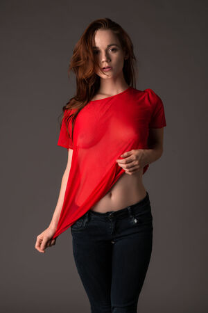 Pretty pale redhead in a red blouse and jeans