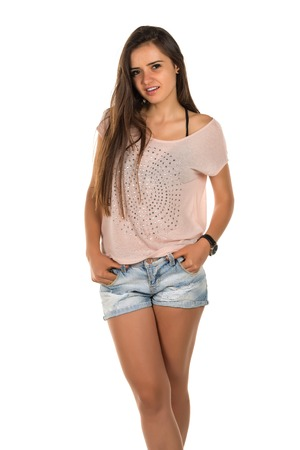 bluejeans: Pretty Romanian brunette in a pink tee shirt and denim shorts Stock Photo