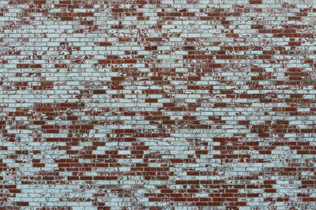 A brick wall, partially covered in white paint