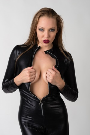 latex fetish: Beautiful slender blonde in a black latex catsuit Stock Photo