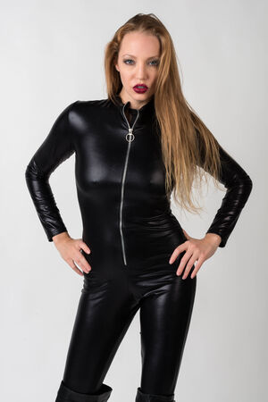 Beautiful slender blonde in a black latex catsuit photo