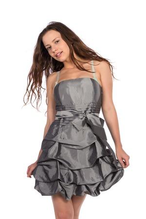 Pretty petite brunette in a gray dress Stock Photo